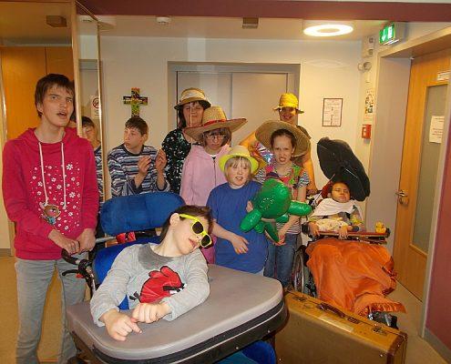 Eine Gruppe von Wohnnest-Gästen verkleidet mit Sonnenbrillen, Strohhüten und Sonnenschirmen
