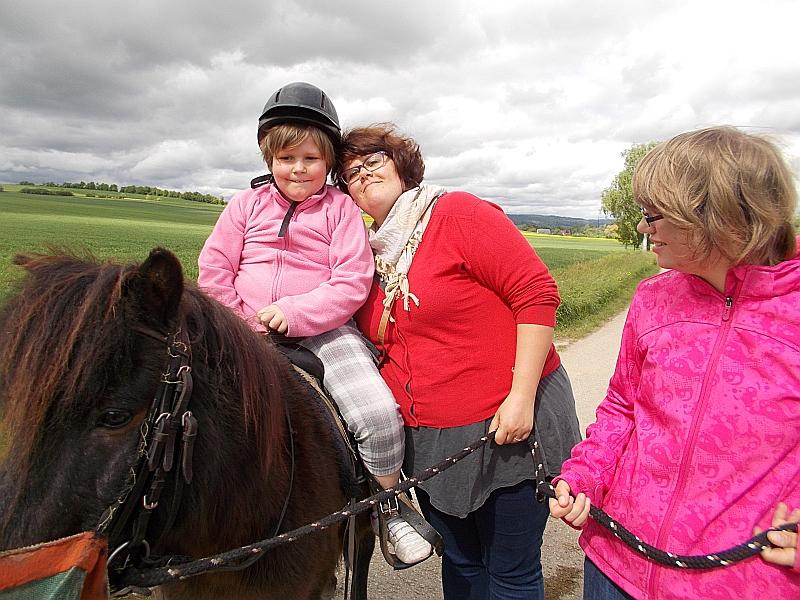 FED-Tagesausflug: ein Mädchen sitzt auf dem Pferd, ein anderes führt